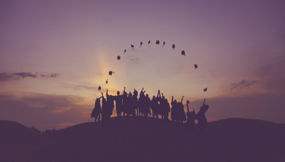 Silhouette of a number of people throwing into their air their graduate hats